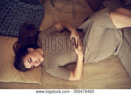 Woman lying down on carpet, happy young adult girl lying on floor