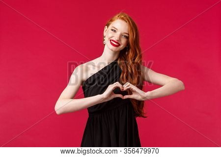 Portrait Of Charming Elegant Caucasian Girl In Red Lipstick, Black Dress With Red Long Hair, Showing
