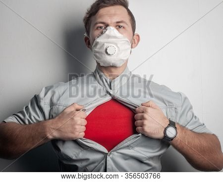 A Superhero In A Red T-shirt And A Medical Mask Tears His Shirt On His Chest, Rushing To Help Victim