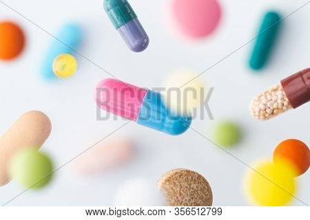 Colorful Pills Flying Above White Background, Levitation Effect