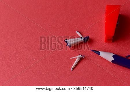 Sharpened Blue Pencil With Sharpener On A Red Background