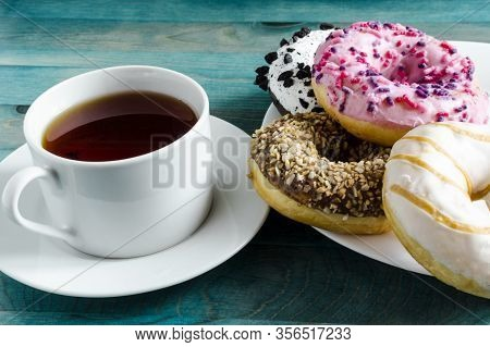 Bright Pink, White And Brown Doughnuts And A Cup Of Tea In A White Bowl On A Green Wooden Background