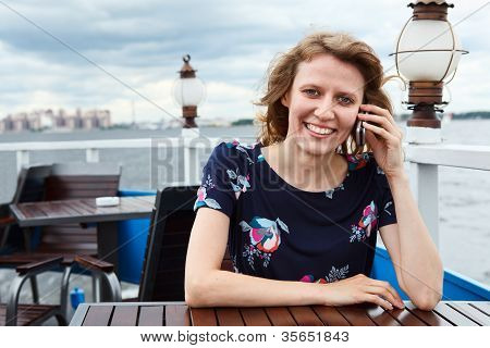 Pretty Caucasian Woman Sitting At The Table With Mobile Phone. Copyspace