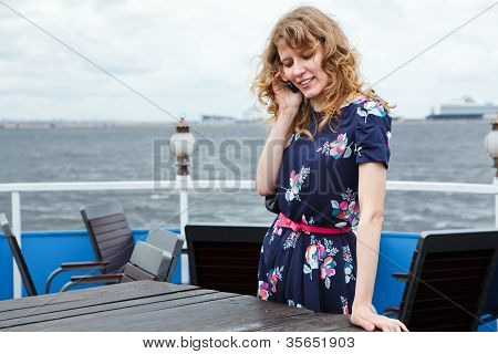 Happy Standing Woman On Ship Deck Cafe With Mobile Telephone