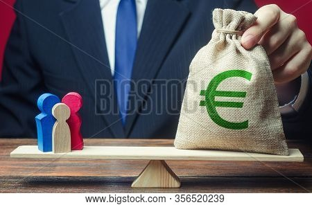 Man Puts Euro Money Bag On Scales With Family Figures. Charitable Donations, Invest In Human Capital