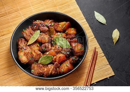 Adobo Pork In Black Bowl At Dark Slate Background. Pork Adobo Or Adobong Baboy Is Filipino Cuisine D