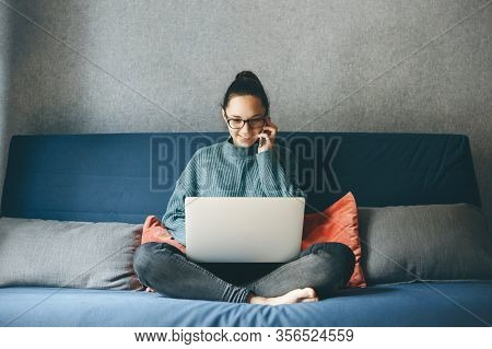 A Girl Works From Home Or A Student Is Studying From Home Or A Freelancer. She Uses A Laptop And A P