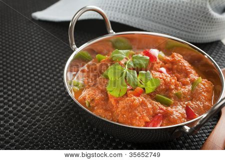 Popular Indian curry Chicken Jalfrezi chicken stir fried with spices with a tomato sauce and red and green capsicums in a balti dish with copy space on left. poster