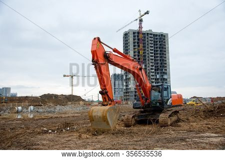 Excavator Working At Construction Site On Earthworks. Backhoe Digs Ground For The Foundation And For