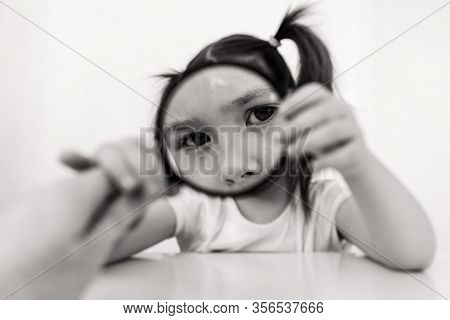 A Child Examines Something Through A Magnifying Glass. A Girl With Two Ponytails Plays Cute. Toddler