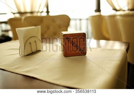 Reserved Sign On The Table. A Wooden Plaque Has A Word Reserved Placed On The Dining Table In A Rest