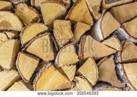Wooden Logs Stacked Together On Top Of Each Other. Wall Of Stacked Wood Logs As Background. Stack Of