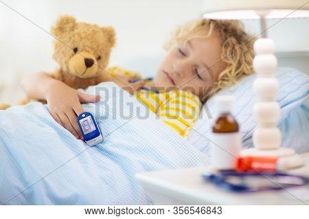 Sick Little Boy With Pulse Oximeter On His Finger. Asthma Treatment. Ill Child Lying In Bed