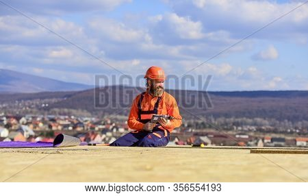 Construction Industry And Waterproofing. Roofer Working On Structure Of Building On Construction Sit