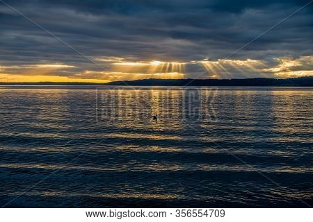 Rays Of Light Shine Down Through Dark Clouds Over The Puget Sound.