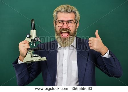 Scientific Research. Teacher With Microscope. Man Hipster Classroom Chalkboard Background. School Te