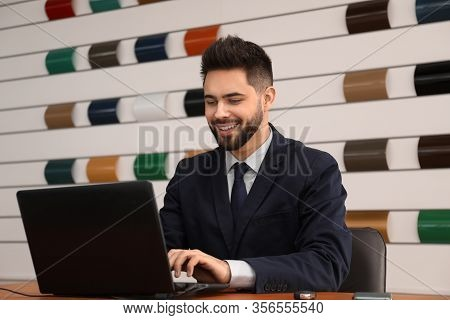 Salesman Working With Laptop At Desk In Car Dealership