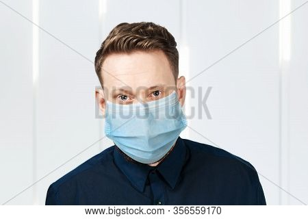 Unhappy, Sad Young Man Wearing A Protective Face Mask Prevent Virus Infection Or Pollution