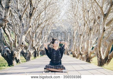 Portrait Of Pretty Asian Woman Sitting Under Plumeria Tunnel In Front Of Nan National Museum In Nan