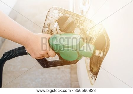 Close-up Of Person Hand Refilling Gas To The Car Tank In Gas Petrol Station.