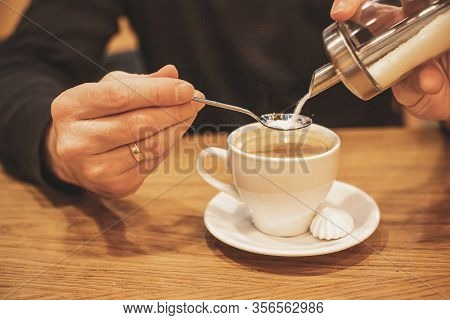 Young Man Hands Holding, Pouring Sugar From Container In Coffee. Selective Focus.mans Hand Pouring S