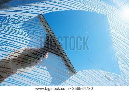 Cleaning Soapy Windows With Squeegee Against Sunny Blue Sky. Spring House Cleaning Concept. Copy Spa