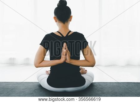 Middle Aged Women Practicing Yoga In Lotus Pose Or Padmasana With Raised Hands Namaste Behind The Ba
