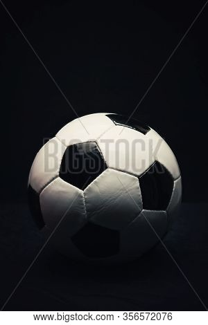 Vertical Photo Of Classic Football Ball Isolated On A Black Background With Copy Space For Publicity