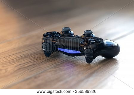 Brecht, Belgium - Februari 1 2020: A Portrait Of A Turned On Playstation 4 Controller With A Blue Li