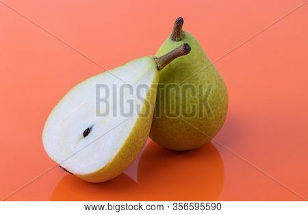 A Pear Cut In Half Together With A Whole Ripe Pear On An Orange Background