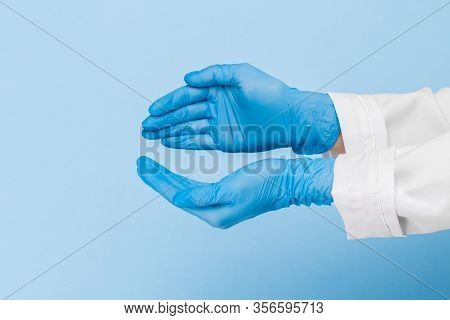 Doctor's Hand In A Blue Medical Glove Holds An Object On A Blue Background. Infection Control. Mocap