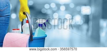 The Concept Of Cleaning Service. A Cleaning Lady Is Holding A Bucket Of Cleaning Products On A Blurr