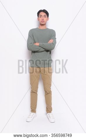 full length young man isolated on white background wearing green sweater and khaki pants full body, full length standing with arms crossed