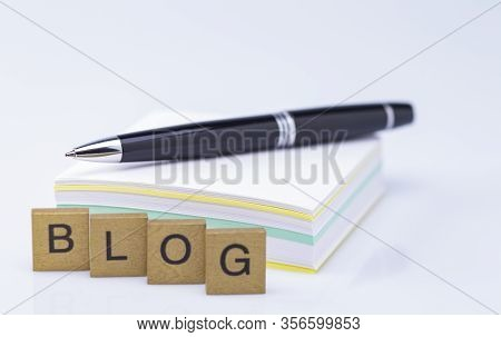 Image Shows A Paper Stack With Pen And Golden Wooden Letters