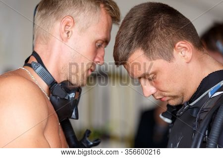 Diving Instructor Helps A Beginner Diver Prepare For Diving. Diver Helps Another Diver Equip Young G