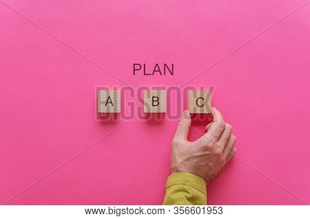 Male Hand Choosing Plan C Out Of Options A, B And C. Over Pink Background.