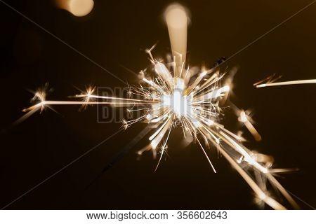 Burning Sparking Stick Starlight Fireworks Pyrotechnic Dark Black Warm Background Held On Hand