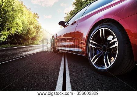 Red sport car on the asphalt road