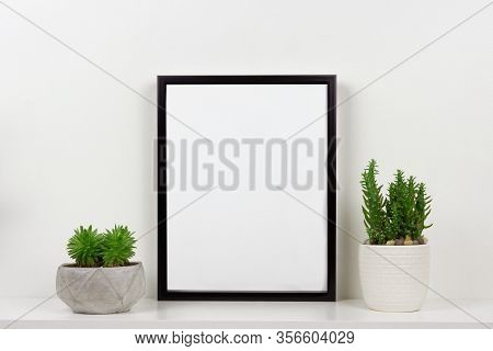 Mock Up Black Frame And Succulent Plants In Pot On A Shelf Or Desk. White Shelf And Wall. Portrait F