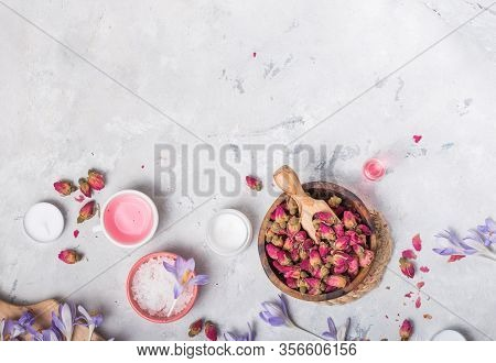 Spa And Wellness Concept With Sea Salt, Dry Roses, Brush, Oil And Towel On Grey  Background, Banner,