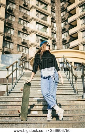 Urban Woman With Skate. Hipster Girl With Skateboard In City. Extreme Sport And Emotions Concept. Al