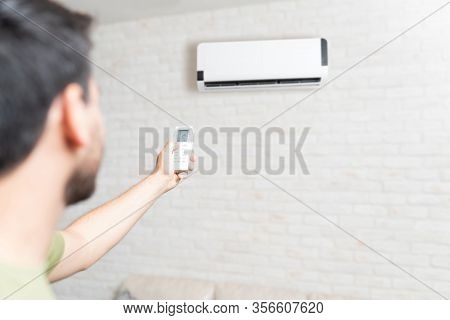 Mid Adult Man Adjusting Temperature Of Air Conditioner Using Remote Control At Home