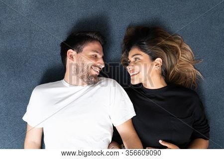 Overhead View Of Smiling Latin Heterosexual Couple Looking At Each Other Lying On Blue Carpet
