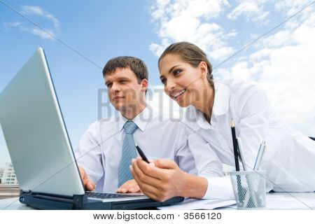 Two successful co-workers sitting in front of laptop outdoors poster
