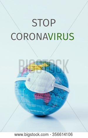 closeup of a terrestrial globe with a protective mask and the text stop coronavirus against an off-white background