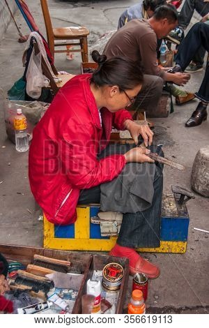 Guilin, China - May 10, 2010: Downtown. Closeup Of Lady In Red Repairing Shoes While 2 Colleagues Ar