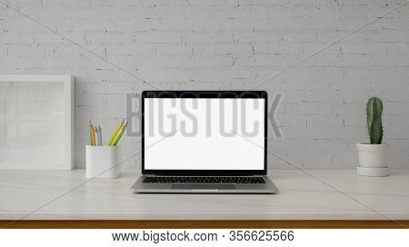 Close Up View Of Minimal Workspace With Mock-up Laptop On Marble Desk With White White Wall