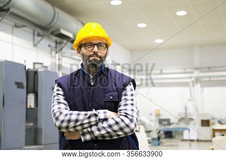Indoor Portrait Of Positive Confident Factory Worker. Bearded Middle Aged Man In Glasses, Hardhat An