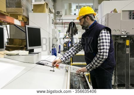 Serious Male Milling Machine Operator At His Workplace In Papermaking Factory Workshop. Bearded Midd