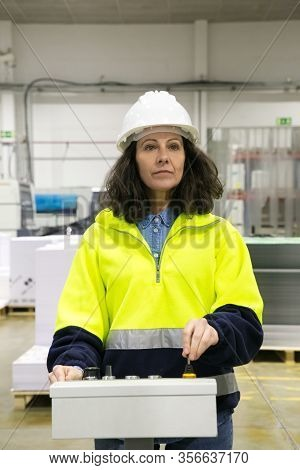 Serious Factory Worker Operating Machine At Control Panel. Middle Aged Woman In Uniform And Hardhat